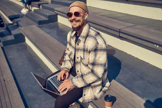 Gelukkige hipsterblogger in stijlvolle brillentypen inhoudstekst om nieuwe volgers aan te trekken naar een eigen website