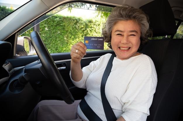 Gelukkige hogere aziatische vrouw die in auto zit en creditcard toont betaalt voor olie, betaalt een band, onderhoud aan de garage, betaalt voor het tanken auto op benzinestation, autofinanciering