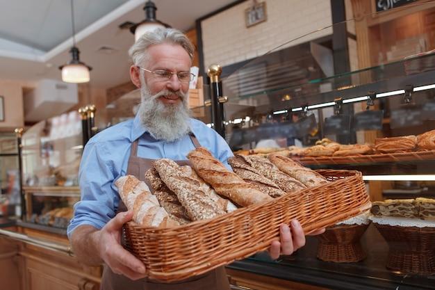 Gelukkige hogere bakker die vreugdevol glimlacht, die vers brood in een mand bekijkt die hij bij zich heeft