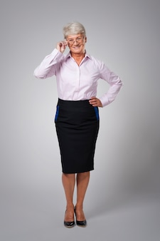 Gelukkige hogere bedrijfsvrouw die glazen draagt