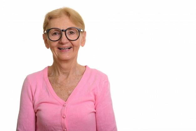 Gelukkige hogere en nerdvrouw die terwijl het dragen van geeky glazen glimlacht lacht