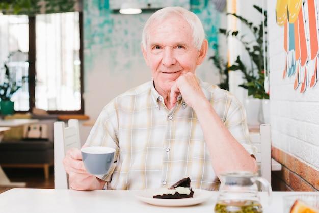 Gelukkige hogere mannelijke zitting in koffie die van thee en dessert geniet