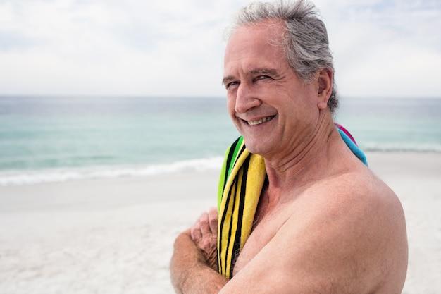 Gelukkige hogere mens die zich op strand met handdoek op schouder bevindt