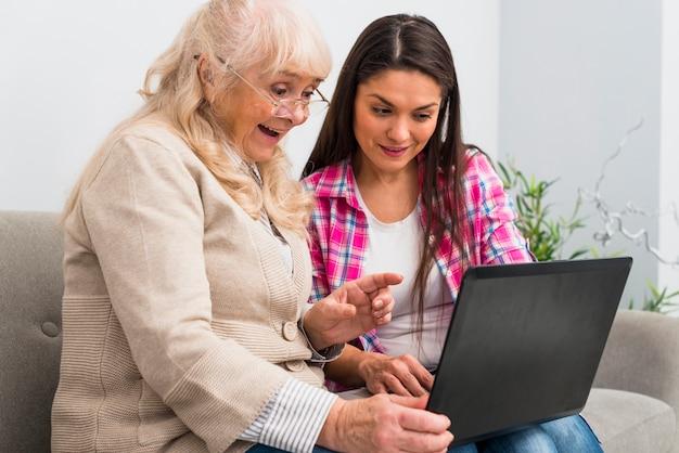 Gelukkige hogere moeder en dochter die laptop bekijken
