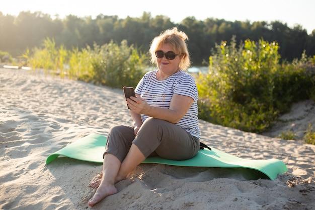 Gelukkige hogere mooie vrouw die smartphonezitting op een zand in de zomerstrand gebruiken