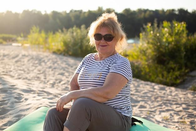 Gelukkige hogere mooie vrouwenzitting op een zand in de zomerstrand