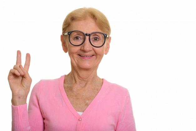 Gelukkige hogere nerdvrouw die terwijl het geven van vredesteken en het dragen van glazen glimlachen
