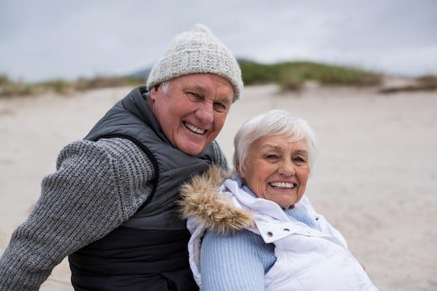 Gelukkige hogere paarzitting samen op strand