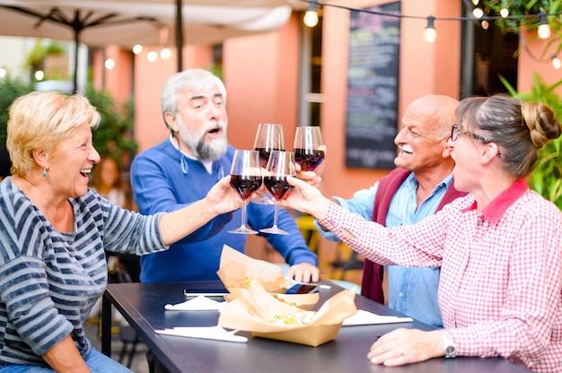 Gelukkige hogere vrienden die en rode wijn glimlachen bij bar roosteren