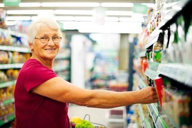 Gelukkige hogere vrouw bij supermarkt