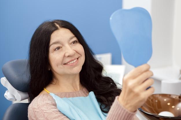 Gelukkige hogere vrouw die aan de spiegel bij de tandkliniek glimlachen