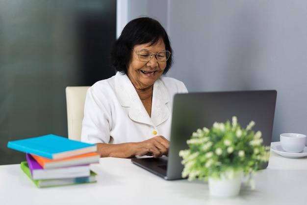 Gelukkige hogere vrouw die aan laptop computer werkt