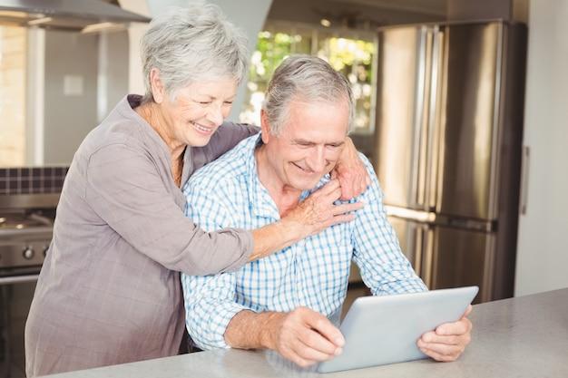 Gelukkige hogere vrouw die de mens omhelst die tablet gebruikt