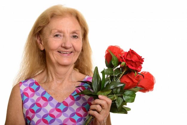 Gelukkige hogere vrouw die en rode rozen glimlacht houdt