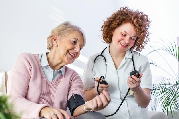 Gelukkige hogere vrouw die haar bloeddruk heeft die in een verpleeghuis door haar verzorger wordt gemeten.