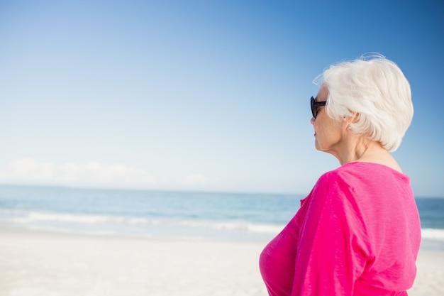 Gelukkige hogere vrouw die met zonnebril water bekijken