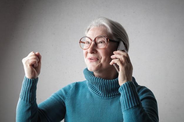 Gelukkige hogere vrouw die op de telefoon spreekt