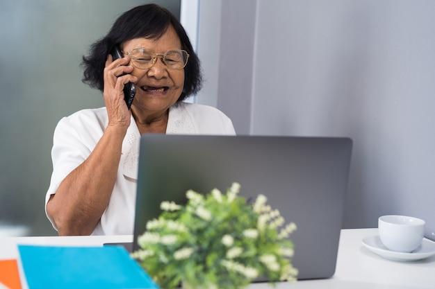 Gelukkige hogere vrouw die op mobiele telefoon spreekt en aan laptop werkt
