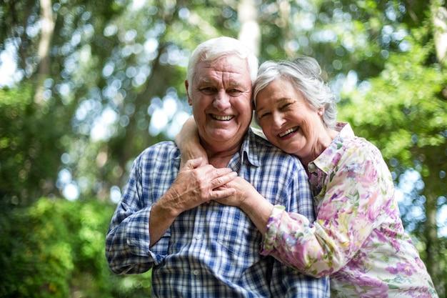 Gelukkige hogere vrouw die van achter echtgenoot tegen bomen omhelst