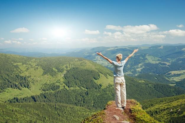 Gelukkige hogere vrouw die van de aard in de bergen geniet