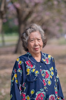Gelukkige hogere vrouw die zich buiten in park bevindt. bejaarde aziatische vrouw die en buiten camera glimlacht bekijkt