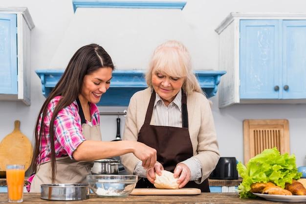 Gelukkige hogere vrouw en haar dochter die het deeg in de keuken voorbereiden