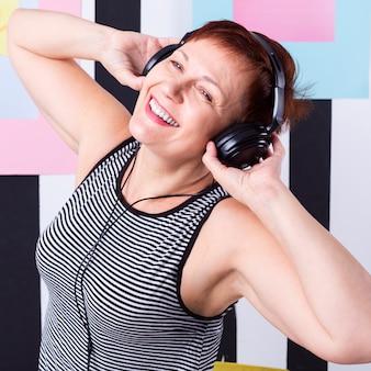 Gelukkige hogere vrouw het luisteren muziek