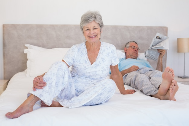 Gelukkige hogere vrouw met de mens op bed