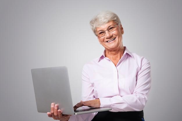 Gelukkige hogere vrouw met eigentijdse laptop