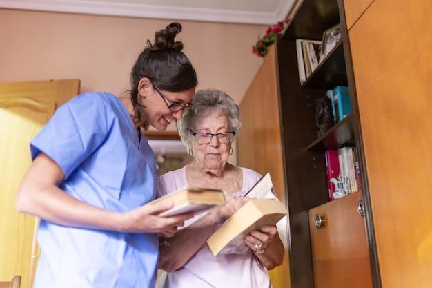 Gelukkige hogere vrouw met haar verzorger die thuis een boek leest