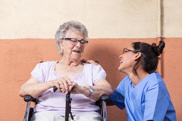 Gelukkige hogere vrouw met wandelstok in rolstoel met haar verzorger thuis