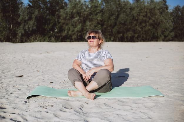 Gelukkige hogere vrouwenzitting op een zand op zonnige dag