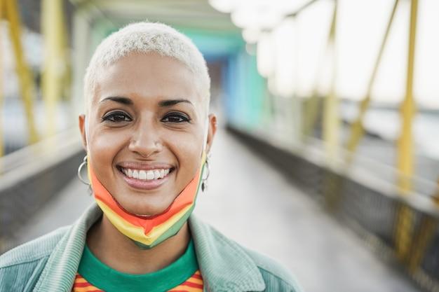 Gelukkige homoseksuele vrouw die lgbt-regenboogmasker draagt - focus op gezicht