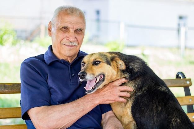 Gelukkige hond gedrukt tegen zijn meester. de hond toont zijn liefde voor eigenaar terwijl hij in park rust