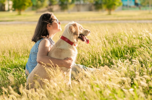 Gelukkige hondretriever en eigenaar die van aard in het park genieten