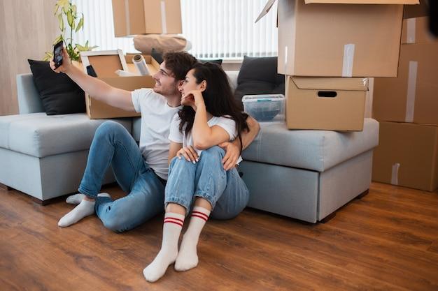 Gelukkige huiseigenaren. paar die selfie met smartphone nemen na zich in nieuw huis te bewegen