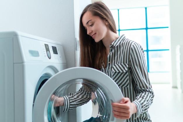 Gelukkige huisvrouw belast met het wassen van kleren en linnen die wasmachine thuis met behulp van