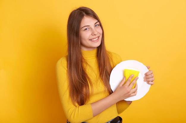 Gelukkige huisvrouw die wasproces demonstreert, witte plaat en spons in handen houdt en vrijetijdskleding draagt