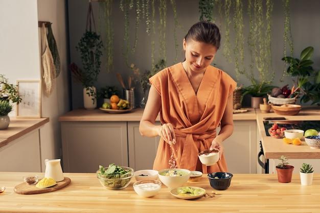 Gelukkige huisvrouw die zelfgemaakte smoothie besprenkelt met kokosvlokken