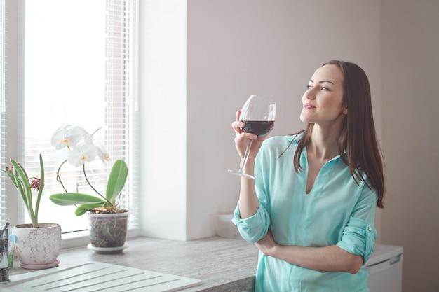 Gelukkige huisvrouw in de keuken met een glas rode wijn die in het venster kijkt