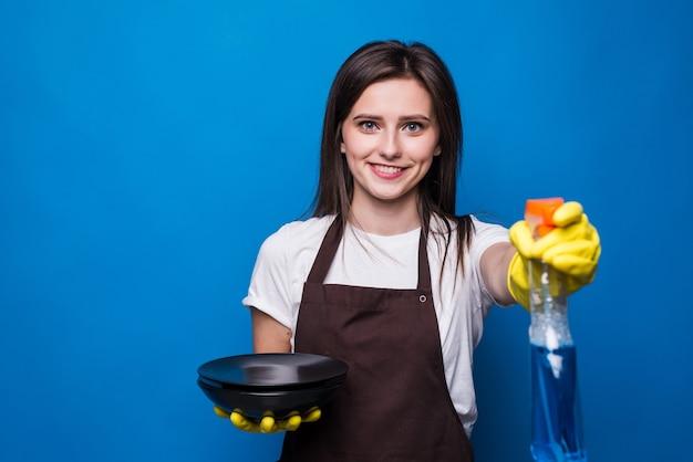Gelukkige huisvrouw in oranje schort met gewassen platen die geïsoleerd afwasmiddel tonen. afwasmiddel in doorzichtige fles in huisvrouw hand in beschermende handschoenen