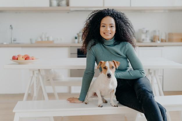 Gelukkige huisvrouw met afro-kapsel, zit op bank met rashond, veel plezier en kijk direct naar de camera