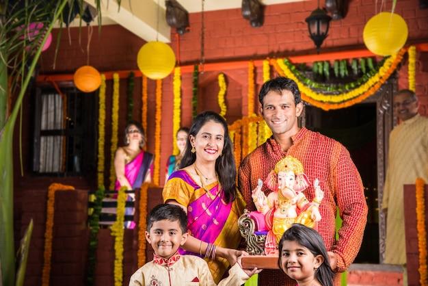 Gelukkige indiase familie die ganesh-festival of chaturthi viert verwelkoming of het uitvoeren van pooja en het eten van snoep in traditionele kleding thuis versierd met goudsbloembloemen