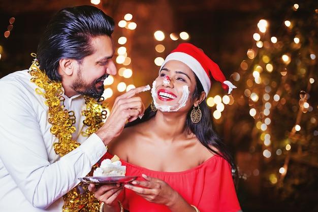 Gelukkige indiase man die cakeroom op het gezicht van de vrouw aanbrengt met kerstmis