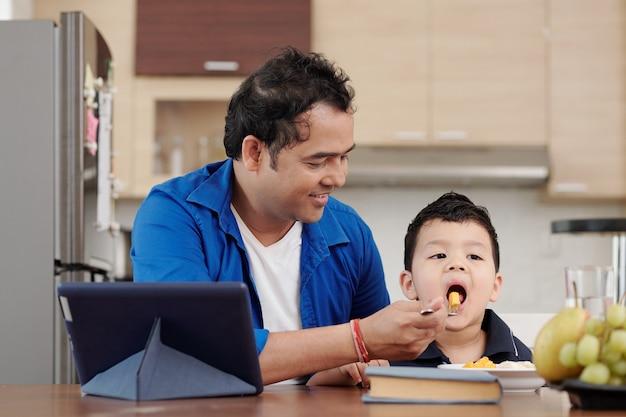 Gelukkige indiase man die zijn zoon voedt met plakjes mango en banaan als ze aan tafel zitten met een digitale tablet