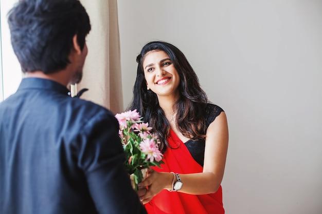 Gelukkige indiase vrouw in sari die bloemen van de man ontvangt