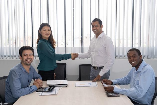 Gelukkige indische en chinese partners die handen op commerciële vergadering schudden