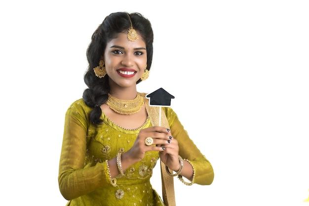 Gelukkige indische traditionele jonge vrouw die een bord van het huisknipsel in haar handen op een witte achtergrond houdt.