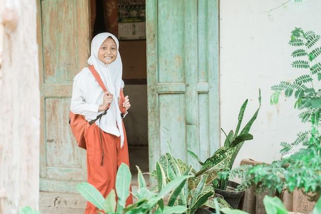 Gelukkige indonesische student die zich 's ochtends voor haar huis klaar maakt om naar school te gaan