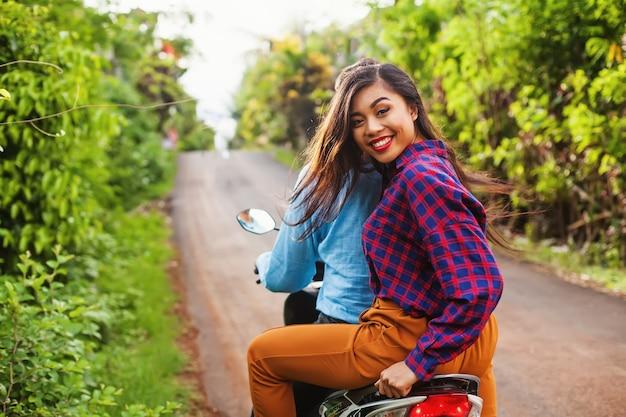 Gelukkige indonesische vrouw die als passagier van motortaxi berijdt